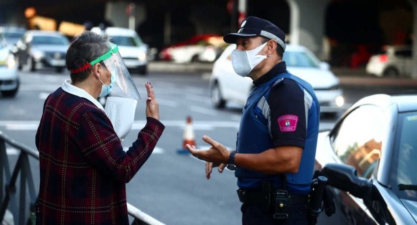 A local police officer speaks with a woman in the Vallecas neighbourhood during the first day of a partial lockdown between and within areas in six districts amid the outbreak of the coronavirus disease (COVID-19) in Madrid, Spain, September 21, 2020. REUTERS/Sergio Perez