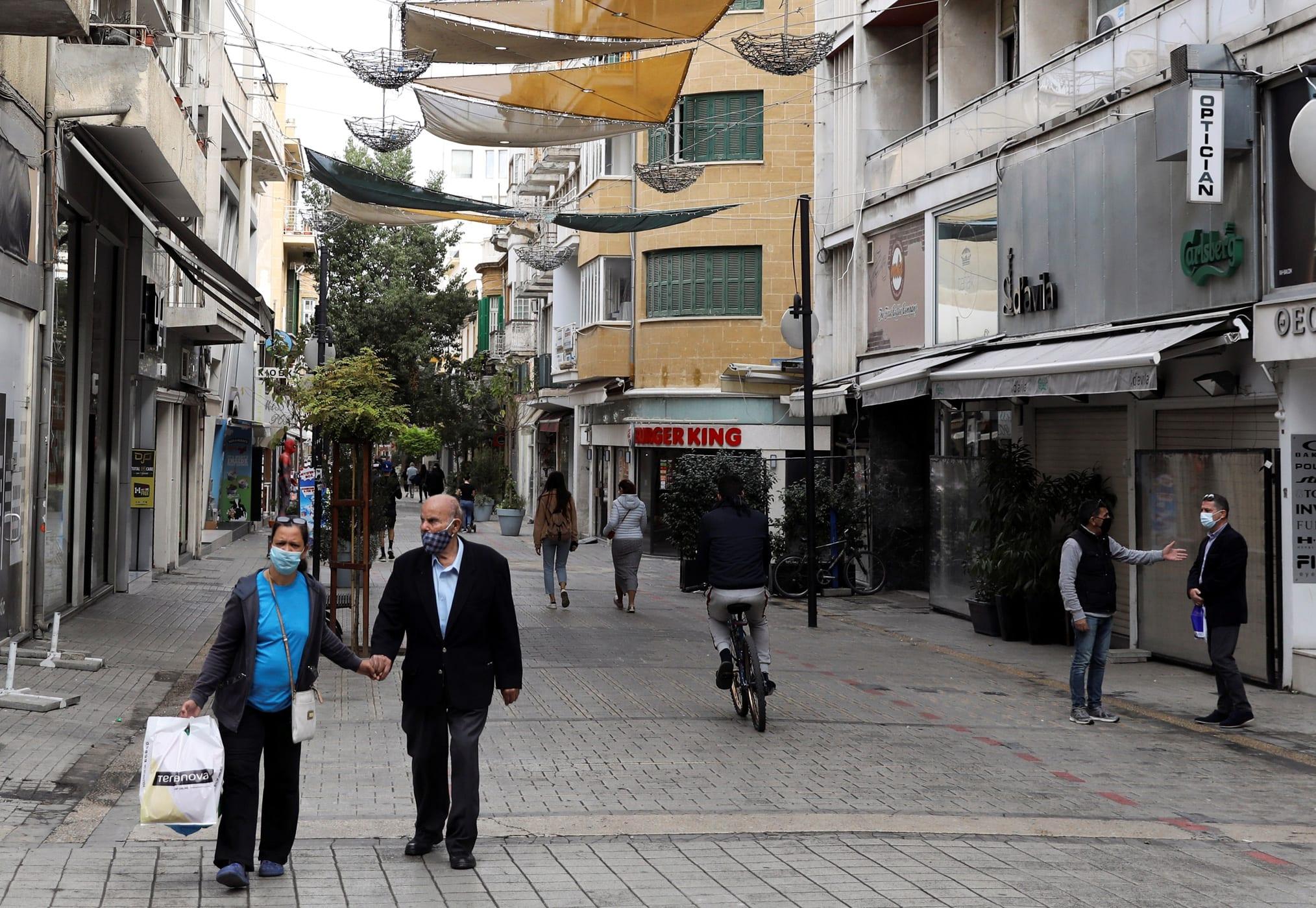 People wearing protective face masks walk in Ledra Street, a main shopping street in Nicosia, amid the coronavirus disease (COVID-19) pandemic, Cyprus December 11, 2020. REUTERS/Yiannis Kourtoglou