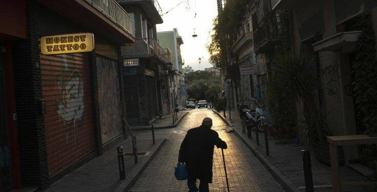 An elderly man walks along a nearly empty street of Psiri, in central Athens, on Tuesday, Dec. 1, 2020.  Greece is on lockdown through Dec. 7 but government officials say it is too early to say when schools and businesses will reopen due to continued pressure on the state-run health service, with intensive care wards near capacity in parts of the country. (AP Photo/Petros Giannakouris)