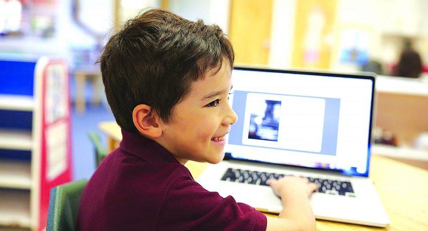 Keeping-children-safe-online_young-boy-smiling-laptop-online-safety