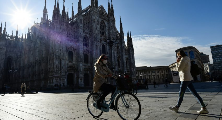 People passes by the Duomo Cathedral, after Lombardy was downgraded from a red to an orange zone, loosening the coronavirus disease (COVID-19) restrictions including allowing non-essential shops to re-open, in Milan, Italy, April 13, 2021. REUTERS/Flavio Lo Scalzo