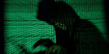 A hooded man holds a laptop computer as cyber code is projected on him in this illustration picture taken on May 13, 2017. Capitalizing on spying tools believed to have been developed by the U.S. National Security Agency, hackers staged a cyber assault with a self-spreading malware that has infected tens of thousands of computers in nearly 100 countries. REUTERS/Kacper Pempel/Illustration     TPX IMAGES OF THE DAY