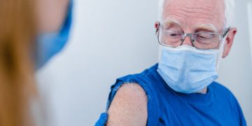 Close up photo of senior man`s arm with doctor`s hands making injection. Elderly patient wearing mask to stop coronavirus spread