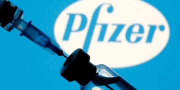 FILE PHOTO: A vial and syringe are seen in front of a displayed Pfizer logo in this illustration taken January 11, 2021. REUTERS/Dado Ruvic/Illustration/File Photo