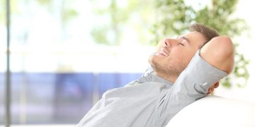 65029250 - side view of a happy attractive man resting and breathing sitting on a couch at home with a window with a green background outdoors