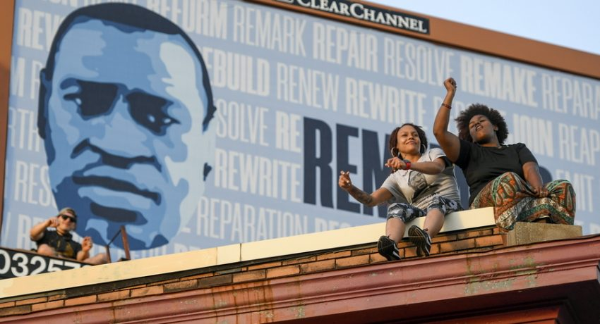 epaselect epa09228183 Two women sit on the roof of Cup Foods and listen to the music performed at George Floyd's Square as hundreds gather at 38th Street and Chicago Ave., the sight where Floyd was killed in 2020, during the commemoration of the anniversary of Floyd's death, in Minneapolis, Minnesota, USA, 25 May 2021. Exactly one year has passed since George Floyd was killed in Minneapolis, Minnesota, after now-convicted former police officer Derek Chauvin kneeled on Floyd's neck for nine minutes, twenty-nine seconds. The year has seen a protest movement which became global and has impacted political elections, police tactics and budgets as well as investigations and prosecutions of similar cases.  EPA/CRAIG LASSIG