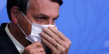 Brazil's President Jair Bolsonaro looks on as he adjusts his protective face mask during a ceremony launching a program to expand access to credit at the Planalto Palace in Brasilia, Brazil, August 19, 2020. REUTERS/Adriano Machado
