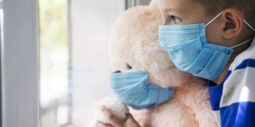 Sad child and his teddy bear both in protective medical masks looks out window. Virus protection, coronavirus pandemic. Coronavirus covid-2019.